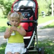 Blond little girl drinking juice with straw — ストック写真