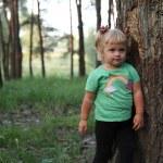 Cute little blonde girl near a tree — Stock Photo
