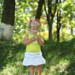 Blond little girl drinking juice with straw — Photo