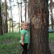 Cute little blonde girl near a tree — Stock Photo #30147705