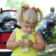 Blond little girl drinking juice with straw — Foto de Stock