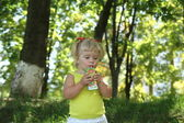 Blond little girl drinking juice with straw — Stock Photo