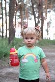 Little girl drinking from plastic bottle — Stock Photo