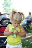 Blond little girl drinking juice with straw — Стоковое фото