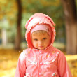 Sad little girl in autumn park — Stock Photo