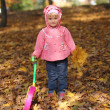Little girl playing in autumn park — Stock Photo