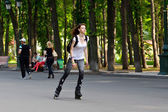 Young girl on roller-skates in city park — Stock Photo