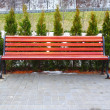 Royalty-Free Stock Photo: Red bench and cypress