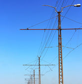 Railroad railway catenary lines against clear blue sky. — Stock Photo