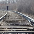 Man walking on railroad tracks - Stock Photo