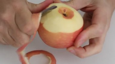 Men's hands cut peel red apple, metal knife, continuously. — Stockvideo