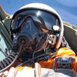 Military pilot in the plane in a helmet in dark blue overalls ag — Stockfoto