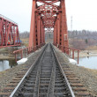 Red metal railway bridge across river. — Stock fotografie #25755075