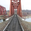 Stockfoto: Red metal railway bridge across river.