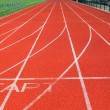Stock Photo: Red treadmill at stadium with white lines