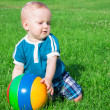 Little boy plays on a green meadow — Stock Photo