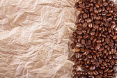 The fried beans of coffee on a crushed paper background — Stok fotoğraf