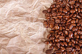 Beans of coffee on a crushed paper background — Stock Photo