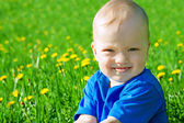 Small child the boy plays on a green meadow — Stock Photo