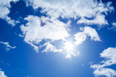 The blue sky with white clouds and the sun — Stock Photo