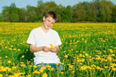 The boy the teenager on a blossoming meadow — Stockfoto