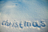Background from inscription Christmas on snow — Stock Photo