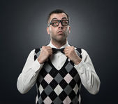 Funny nerd adjusting bow tie — Stock Photo