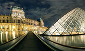The Louvre museum at night in Paris — Stockfoto