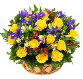 Natural yellow roses and blue irises in a basket — Stock Photo