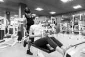 Young woman with an instructor in the gym — ストック写真