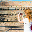 Young female tourist takes a picture inside the Coliseum in Rome — Stock Photo #47032675