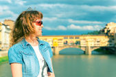 Young female tourist on the background of the Ponte Vecchio in F — Stok fotoğraf