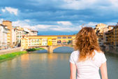 Young female tourist looks at the Ponte Vecchio in Florence — Stok fotoğraf