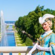 Actress in ancient costume welcomes tourists in Petrodvorets at — Stock Photo #48313737