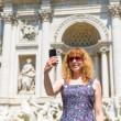 Selfie of a young female tourist on the background of the Trevi Fountain in Rome — Stock Photo #48891673