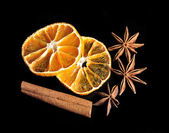 Dried citrus, anis stars and cinnamon on black background — Stock Photo