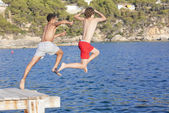 Summer camp kids jumping in sea — Stock Photo