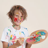 Messy kid with paint pallete — Stok fotoğraf