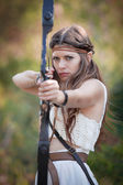 Elf mythical girl shooting bow and arrow — Stock Photo
