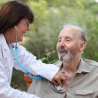 Dr with stethoscope checking senior patient. — Stock Photo