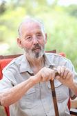 Elderly man with walking stick sitting in garden — Stock Photo