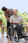 Elderly man out for walk in wheelchair — Stock Photo