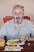 Senior eating healthy meal in residential care home — Stock Photo