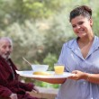 Home carer serving meal to elderly man — Stock Photo