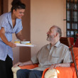 Nurse or helper in residential home giving food to senior man — Stock Photo