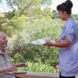 Carer giving senior food in residential home — Stok fotoğraf #47526135