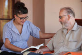 Companion or granchild reading to senior or grandfather — Stock Photo