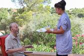 Carer giving senior food in residential home — Stock Photo