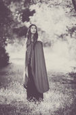 Fiction woman in cloak in forest. — Stock Photo