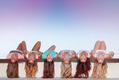 Happy teens with long healthy hair laying upside down.  — Stock Photo